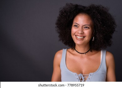 Studio shot of young multi-ethnic African American woman against gray background