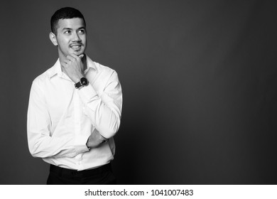 Studio shot of young multi-ethnic Asian businessman wearing white shirt against gray background in black and white