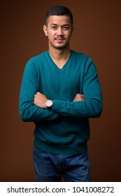 Studio shot of young multi-ethnic Asian man wearing blue long sleeved shirt against brown background