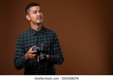 Studio shot of young multi-ethnic Asian man with camera against brown background