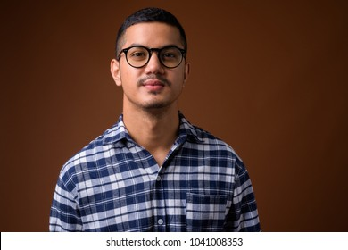 Studio shot of young multi-ethnic Asian man wearing blue checkered shirt with eyeglasses against brown background