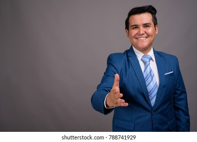 Studio shot of young multi-ethnic businessman wearing blue suit against gray background