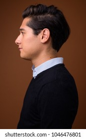 Studio shot of young multi-ethnic handsome man looking smart against brown background