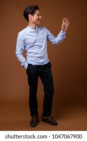 Studio shot of young multi-ethnic handsome businessman against brown background