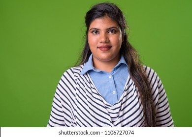 Studio shot of young overweight beautiful Indian businesswoman against chroma key with green background