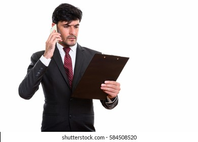 Studio shot of young Persian businessman reading on clipboard while talking on mobile phone