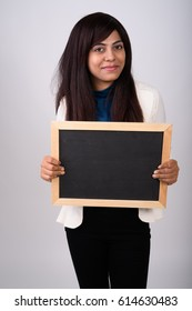 Studio shot of young Persian businesswoman standing while holding blank blackboard against gray background