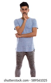 Studio shot of young Persian man standing while thinking