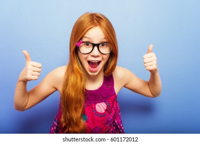Studio shot of young preteen 9-10 year old redhead girl wearing eyeglasses, standing against blue purple background, big thumbs up, excited facial expression