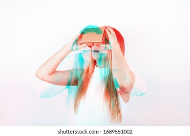 studio shot of a young, professional female model looking through cardboard virtual reality (VR) headset, isolated on white. 3D anaglyph effect, glitch art with double exposure.