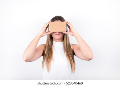 studio shot of a young, professional female model looking through cardboard virtual reality (VR) headset, isolated on white