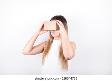 studio shot of a young, professional female model looking through cardboard virtual reality (VR) headset, isolated on white. angle view
