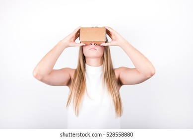 studio shot of a young, professional female model looking through cardboard virtual reality (VR) headset, isolated on white. head up