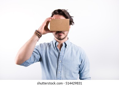 studio shot of a young, professional man looking through cardboard virtual reality (VR) headset, isolated on white background
