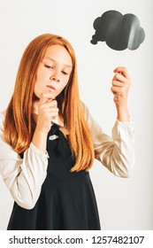 Studio shot of young red-haired kid girl holding paper thinking bubble, posing on white background