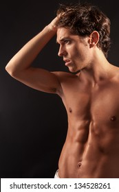 Studio shot of a young sexy male adult looking to the side with one hand on the head.