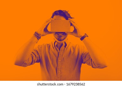 studio shot of a young, smiling model looking through cardboard virtual reality (VR) headset, isolated on white. duotone effect in orange colours.