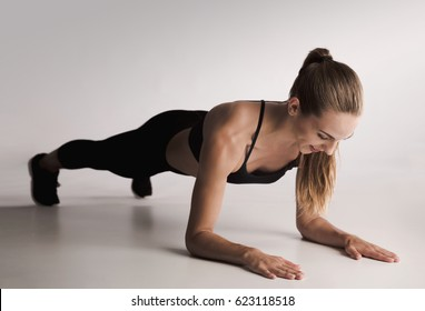 Studio shot of a young woman doing plank exercises