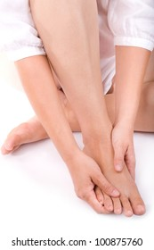 Studio shot of a young woman massaging her foot