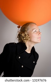 A studio shot of a young woman posing with a large orange balloon.