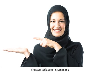 studio shot of young woman wearing traditional arabic clothing. she's holding her hand to the side so you can photoshop in your own content, like a product box or something similar