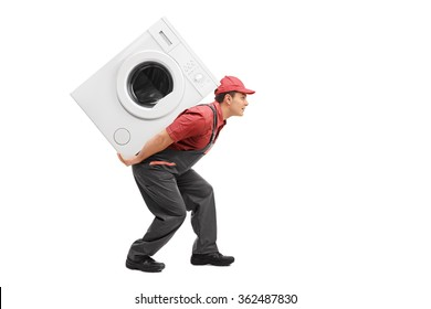 Studio shot of a young worker carrying a washing machine on his back isolated on white background