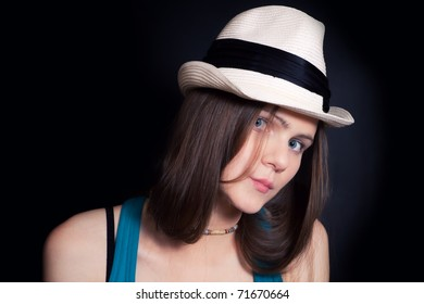 Studio shoulder portrait of young blue-eyed girl in white hat on black background