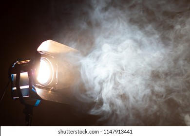 Studio spotlight using for background production film . led lights with blurred smoke texture in dark room . electric tools set for photography , video maker , cinematography