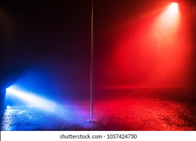 Studio stage with pole for dancing in center. Blue and red lights. Water effect.