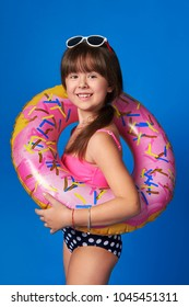 Studio summer portrait of child girl in swimsuit, sunglasses, inflatable ring. Lovely face young woman smile, season beach holiday. Little girl 8 years rubber ring isolated Blue background.