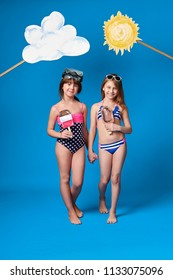 Studio summer portrait full length young girls friends. Beautiful children posing in swimsuits, slim body, ice cream painted. Fashion kids go together,holding hands. Blue background, studio.