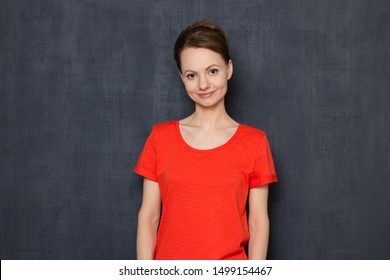 Studio waist-up portrait of cute caucasian fair-haired girl wearing orange T-shirt, smiling and looking kindly at camera, holding hands along body, being in good mood and happy, over gray background