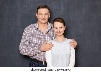 Studio waist-up portrait of happy couple, dressed in casual clothes, man is putting his arms around woman's shoulders, both are looking cheerfully at camera, over gray background. Relationship concept