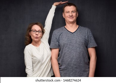 Studio waist-up shot of amazed short woman pulling up and showing with hand at height of tall man standing beside her, smiling and looking at camera, over gray background. Variety of person's heights - Shutterstock ID 1468274624