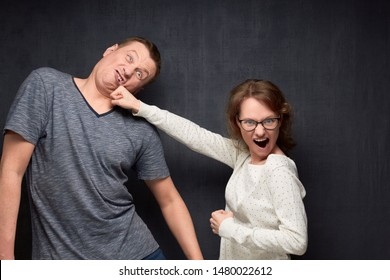 Studio waist-up shot of furious woman screaming and beating perplexed man grimacing and staggering from pain, over gray background. Angry wife and unhappy husband. Funny parody of real fighting