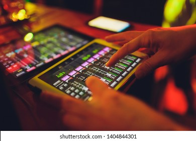 studio working with sound and light mixer console,hands of sound engineer working on recording studio mixer adjusting the volume of a sound mixer audio mixing console with digital mixer tablets.