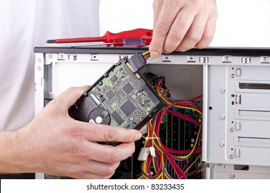 studio-shot of a computer support engineer changing the hard drive of an office computer,isolated on white.
