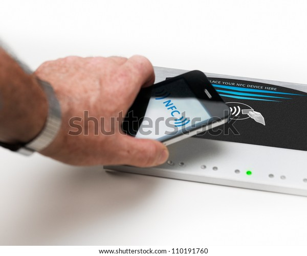 Studioshot of payment action with a mobile phone in front of a NFC terminal