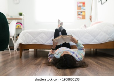 Studious adolescent girl reading a book and enjoying a story in her bedroom. Young teenage girl lying on the floor with her feet up on her bed