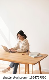 Studious Asian woman working at home using a laptop