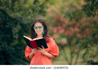 Studious Girl Holding a Book Outdoors in the Park. Female literature student reading bestseller novel outdoors