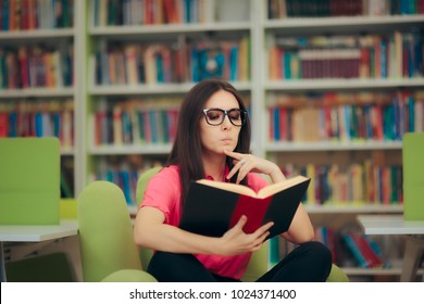 Studious Girl Reading a Book in a Library. Funny woman studying hard and having some questions