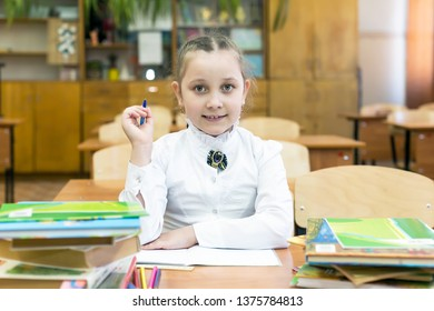 Studious girl schoolgirl in a white blouse. Neat girl schoolgirl sitting at the school desk in the classroom.