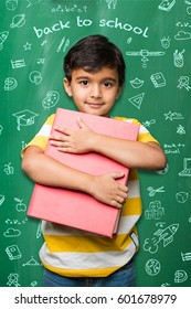 Studious indian/asian school kid holding big book over green chalkboard background with doodles