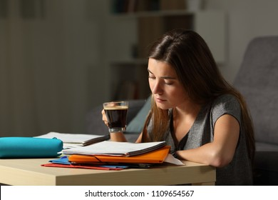 Studious student studying holding a coffee cup in the night at home