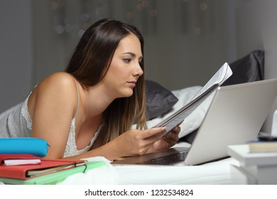 Studious student studying late hours comparing notes lying on the bed in the night at home