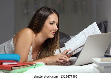 Studious student studying on the bed comparing notes online with a laptop in the night at home