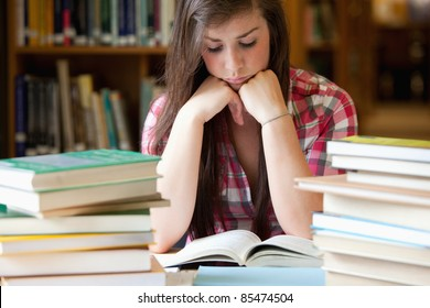 Studious woman surrounded by books in a library