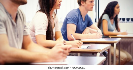Studious young adults listening while sitting at desk in classroom