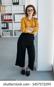 Studious young businesswoman wearing heavy rimmed glasses standing leaning against a wall in the office with folded arms and a thoughtful expression